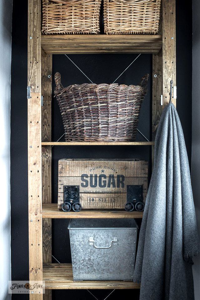 How to turn a new Ikea storage shelf into a rustic farmhouse beauty! The Henjne shelf was stained then stacked with vintage baskets and a crate stenciled with Pure Cane Sugar to house laundry, recycling and more! With Funky Junk's Old Sign Stencils.