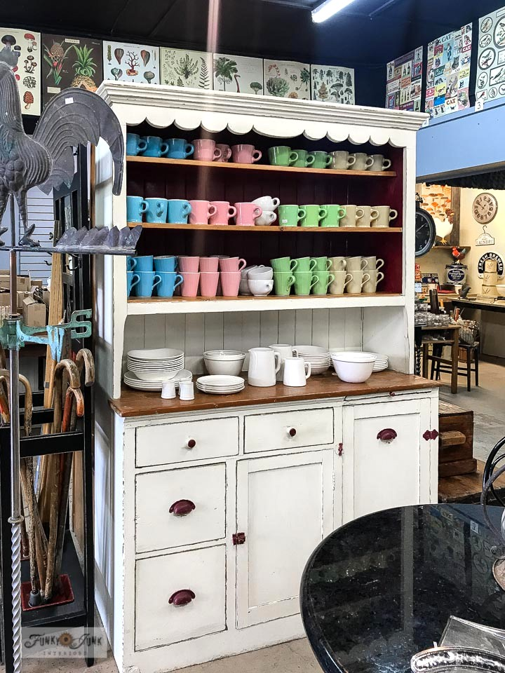Colourful vintage-inspired new coffee mugs in a white vintage cupboard at Switzer's Vintage Decor in Chilliwack, BC Canada