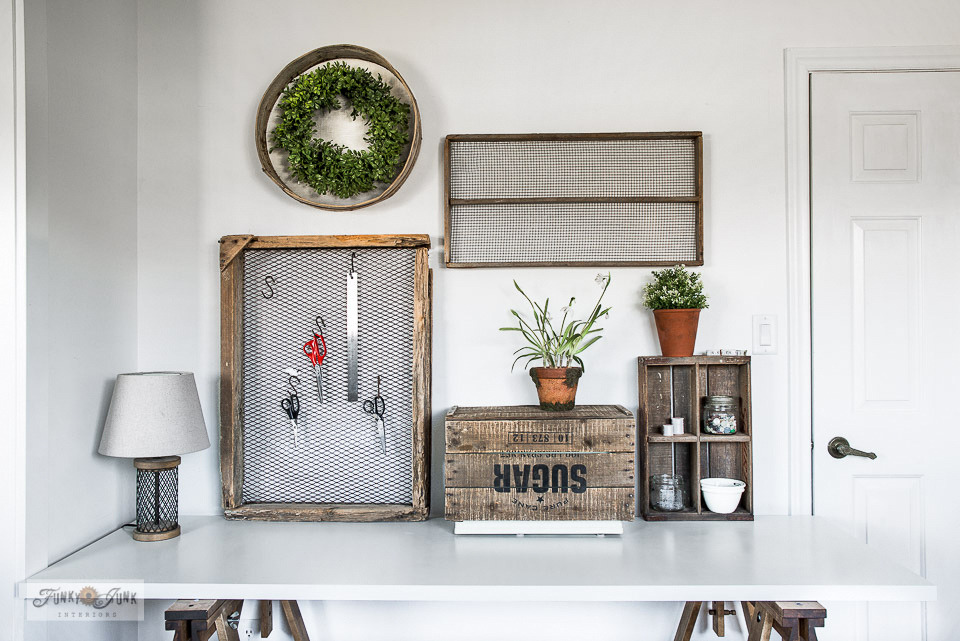 sewing desk with crates and antique soil sifters for sewing accessories and wall art