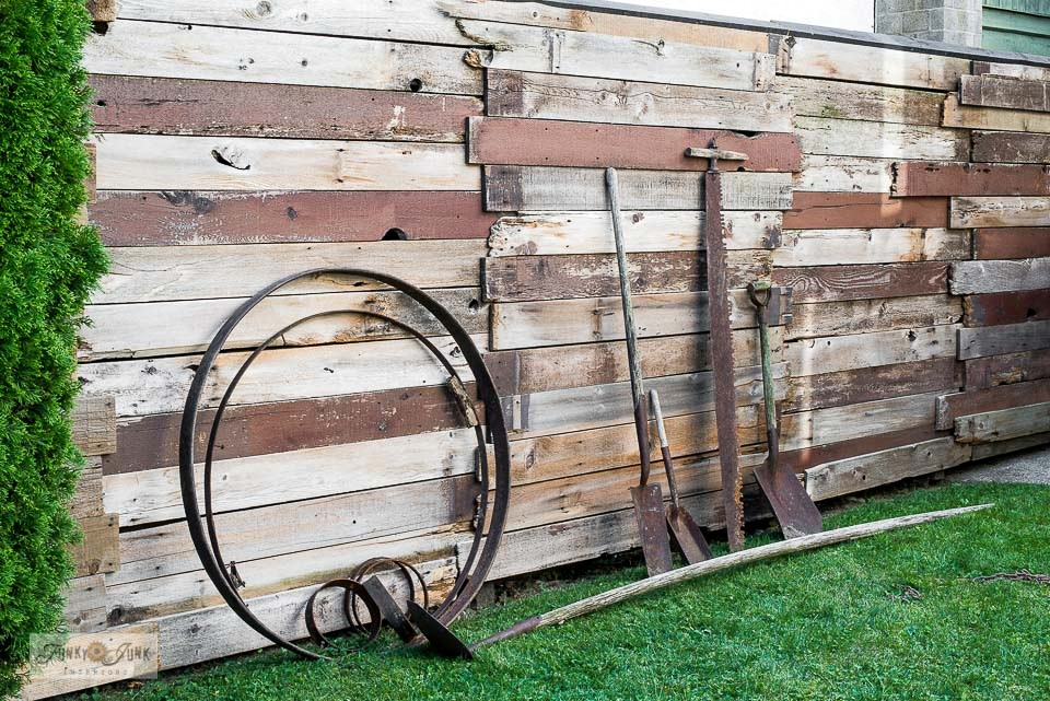 How I decorated my reclaimed wood backyard garden fence with rusty antique tools as garden art. Click for the end results!