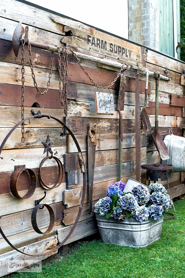 Learn how to build this reclaimed wood fence without cutting any boards! Decorated with rusty garden tools and signs. Click to learn how.