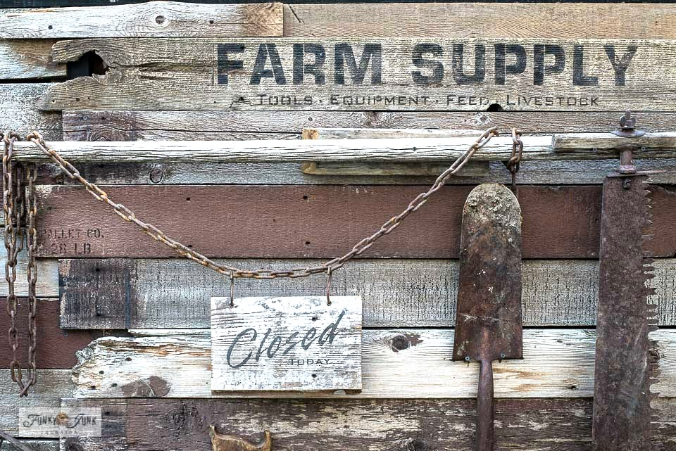 Learn how to build a reclaimed wood rustic garden fence with scrap wood and lettered with a Farm Supply sign stencil from Funky Junk's Old Sign Stencils! #stencils #reclaimedwood #gardenfence #signs