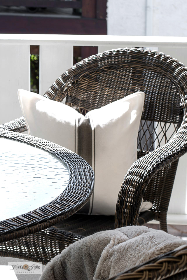 Learn how to create this stenciled grain sack stripe pillow with Ikea covers. Featuring a resin wicker table and chairs on a summer patio.