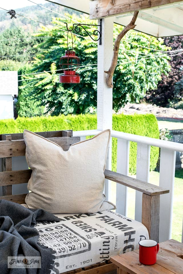 Learn how to make an easy patio chair from two pallets decorated with stenciled subway styled sign fabric.