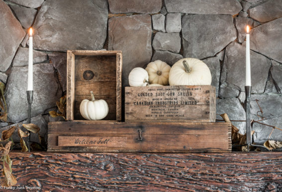 pumpkins and antique welcome fall crates on a fireplace mantel