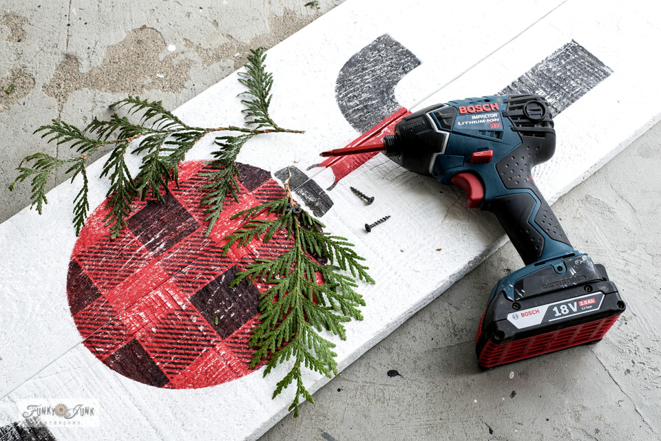 Add 3d effects by attaching evergreen branches to a wood Christmas sign for festive impact!