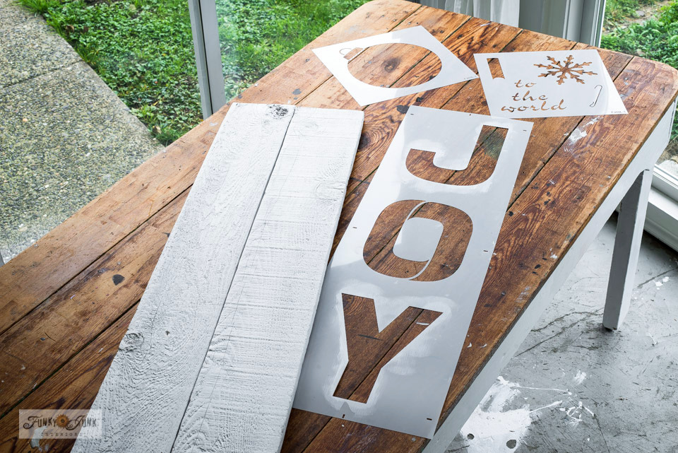 Learn how these painted reclaimed wood fence planks and stencils are about to become a Joy Christmas sign!