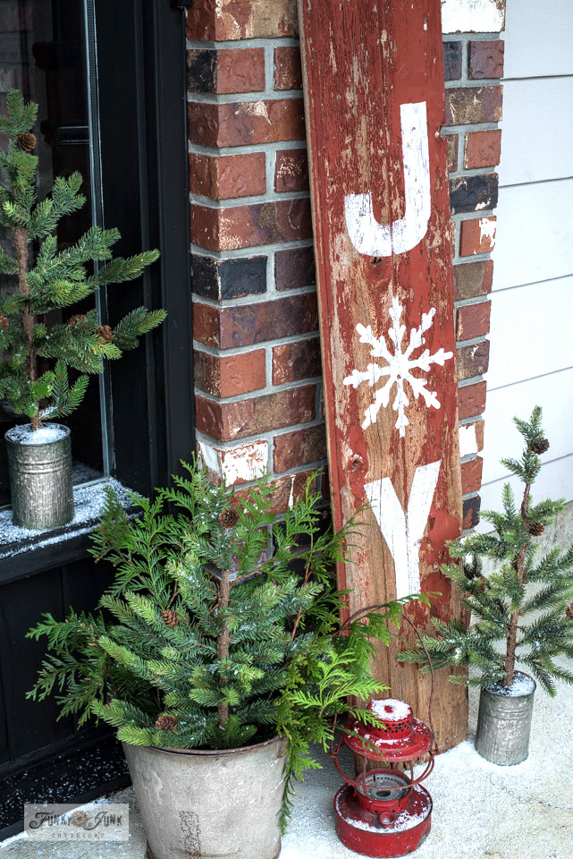 Learn how to stencil this Joy rustic Christmas sign on red chippy barn wood shiplap with Funky Junk's Old Sign Stencils.