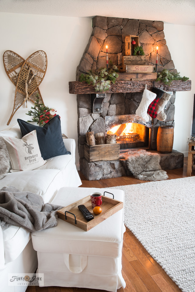Take this Christmas livingroom tour including snowshoe wall art, Reindeer Feed pillow, stacked vintage crate Christmas mantel, Ikea Ektorp white slipcovered sofa and ottoman, plus!