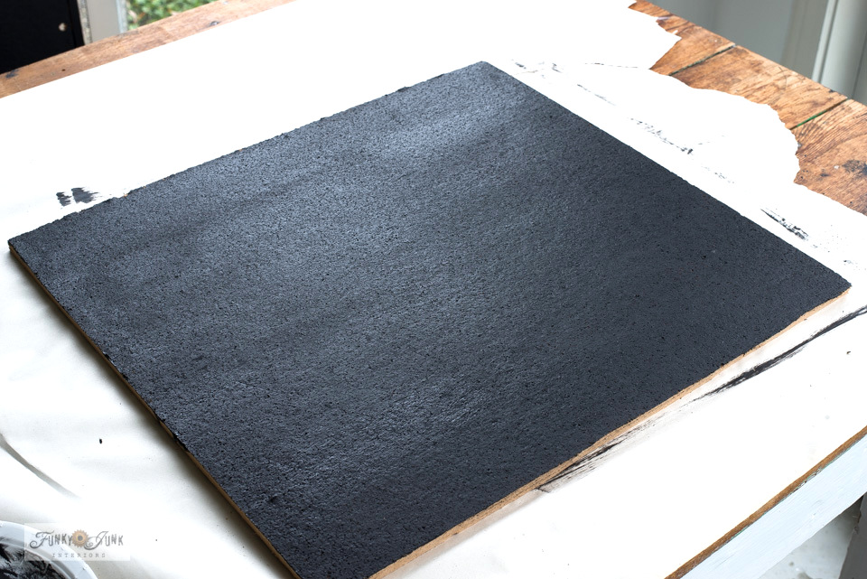Painting out a bulletin board in Fusion's coal black for a chalkboard effect, to create a Christmas countdown bingo board.