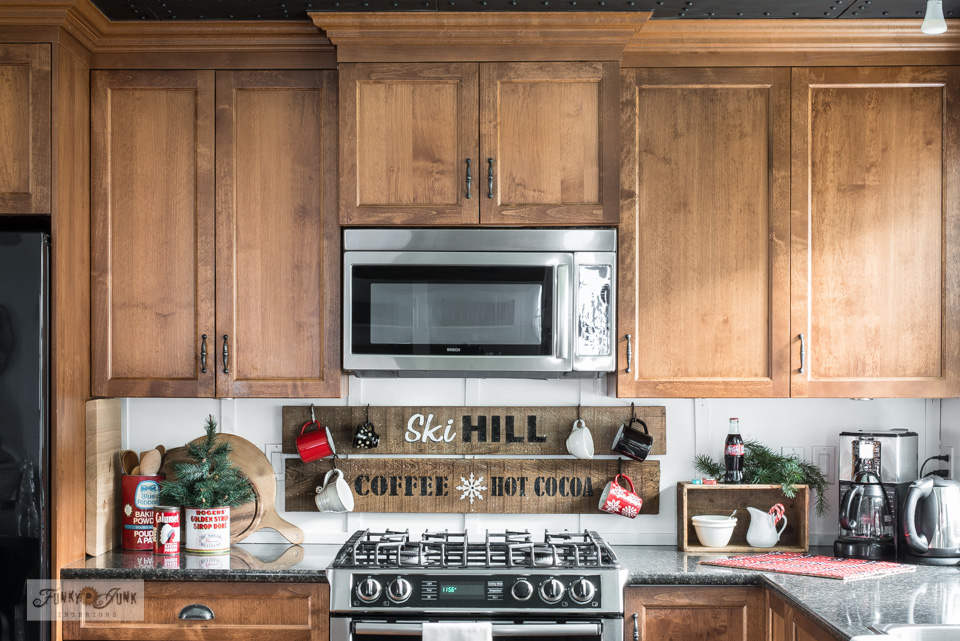 Take this Christmas kitchen home tour which includes a Ski Hill coffee and hot cocoa rustic stenciled sign, crate coffee station, rustic woodsy cupboards, antique tins, and more!