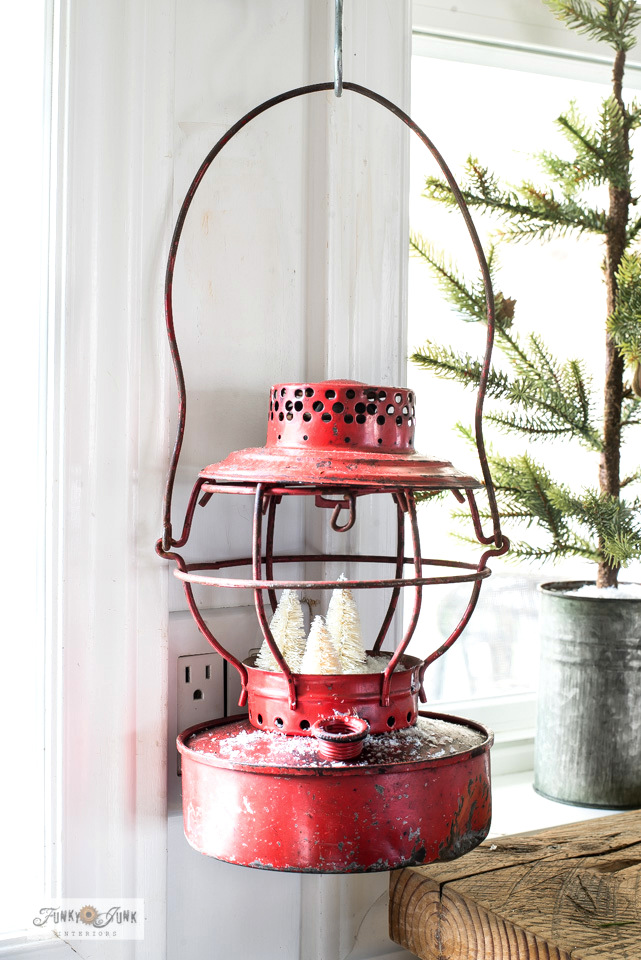 A vintage red metal train lantern turns into a snowy scene with brush bottle trees from a dollar store and faux snow in this Christmas kitchen home tour.