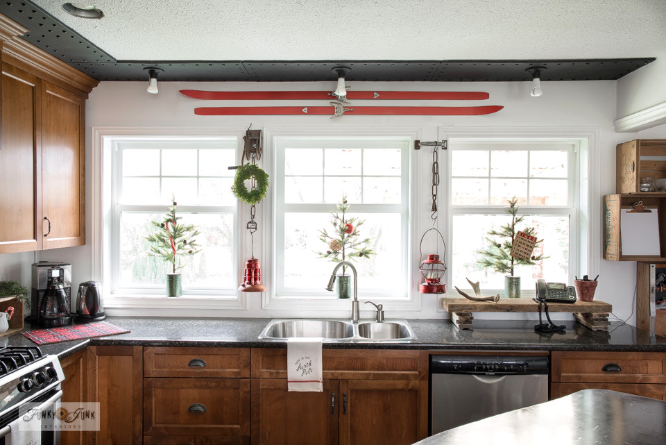 Take this Christmas junk home tour which includes a festive kitchen with red ski window valance, antique red train lanterns, faux tin canned Christmas trees, plus!