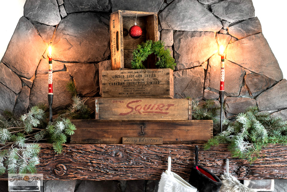 Learn how this rustic stacked vintage crates Christmas mantel was pulled together! With vintage Santa candles, snow-sprayed evergreen branches and Merry Christmas sign. #funkyjunkinteriors #christmasmantel #christmasdecor #rusticchristmas