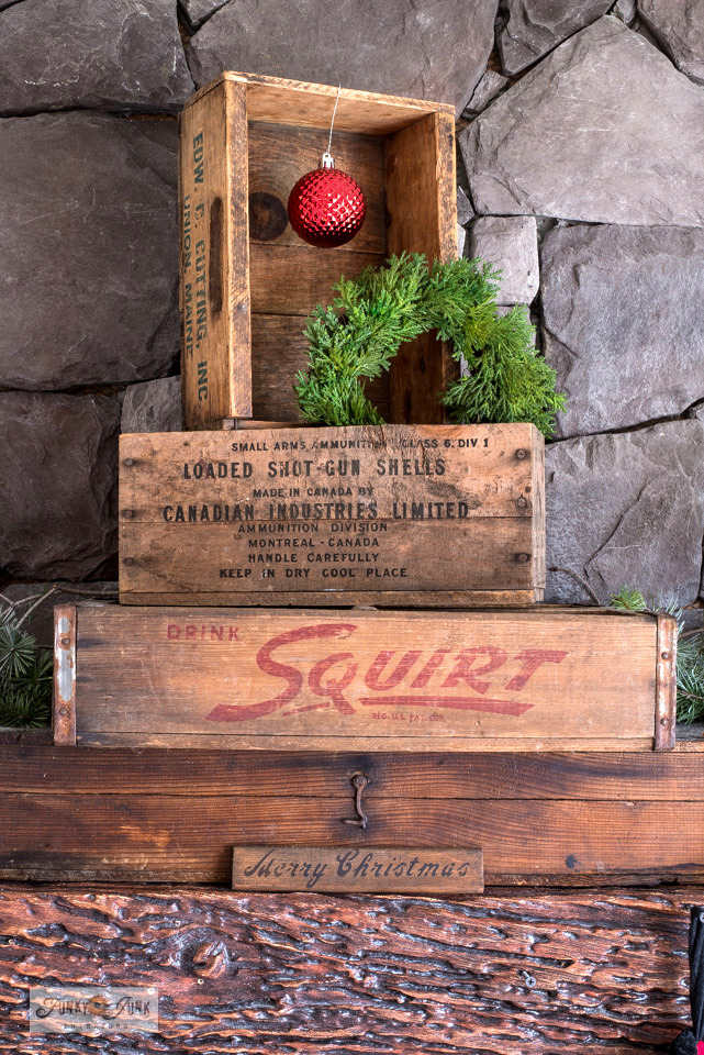 Stacked vintage crates come together to create a charming Christmas fireplace mantel design. Click to check out the vintage Santa candles and more!