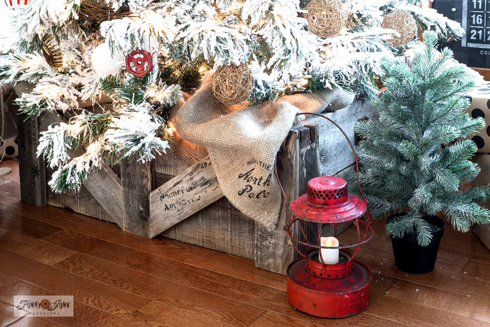 Learn how I DIYed this Flocked Christmas tree with a wood crate tree skirt from pallet and scrap wood! Stenciled like a shipping crate, this year's tree is very farmhouse rustic! Click for full tutorial. #funkyjunkinteriors #christmastrees #Christmastreeskirt