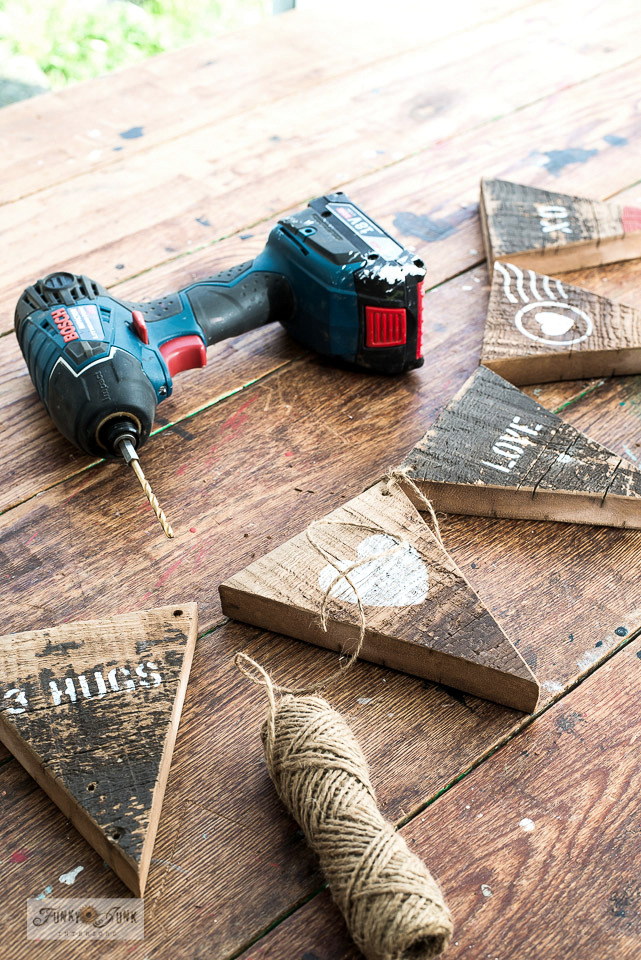 Predrilling holes with a Makita drill to hang a rustic reclaimed wood Valentine's Day banner. #valentinesday #valentines #banner #pennant