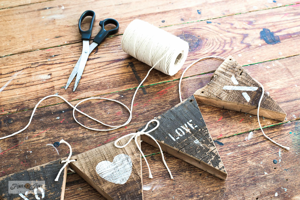 Tieing together a reclaimed wood Valentine's Day banner with heavy white string.