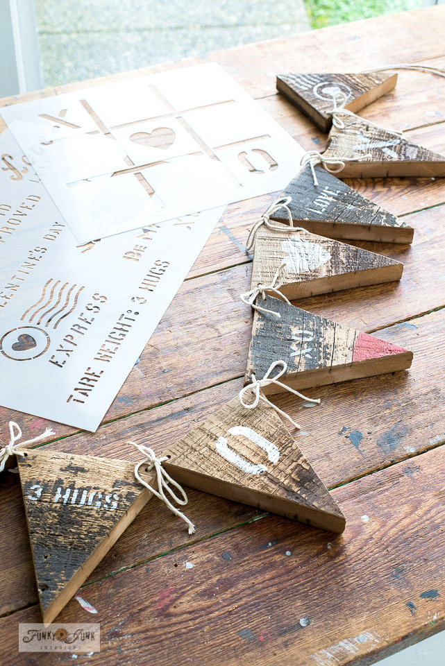 Learn how to make this rustic reclaimed wood Valentine's Day banner with valetine messages with Funky Junk's Old Sign Stencils Valentine Crates and Tic Tac Toe! #funkyjunkinteriors #valentinesday #valentines, #banner #pennant #stencils #funkyjunksoldsignstencils #oldsignstencils