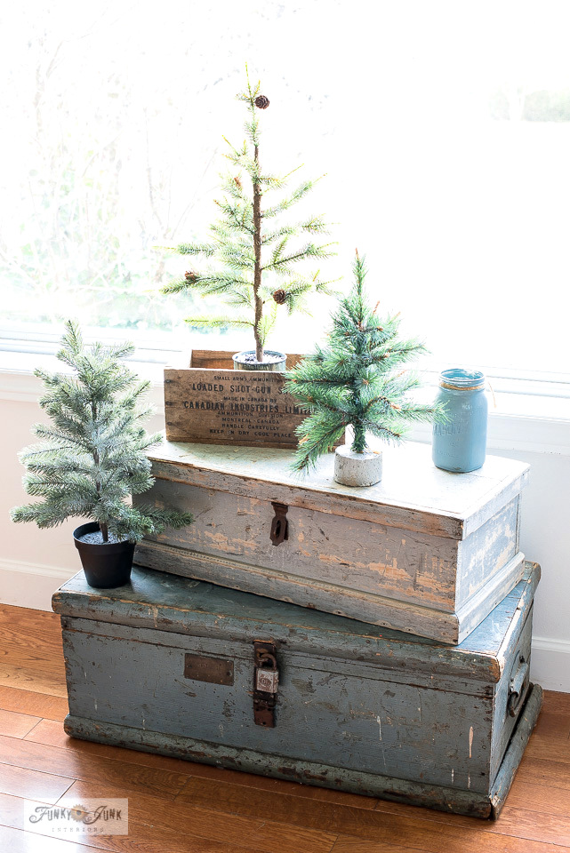 Stacked powder blue vintage trunks with faux pine trees offer the perfect winter decorating ambiance to this ski-themed winter living room tour!