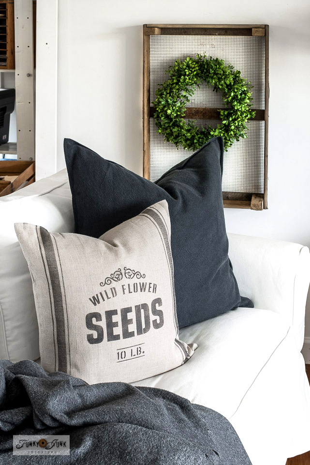 Learn how to stencil this vintage-inspired Wild Flower Seeds grain sack pillow for spring and summer decorating! With an Ikea pillow cover, and Funky Junk's Old Sign Stencils. Click to visit full tutorial with short how-to video! #springdecorating #pillows #stencils #ikeahack