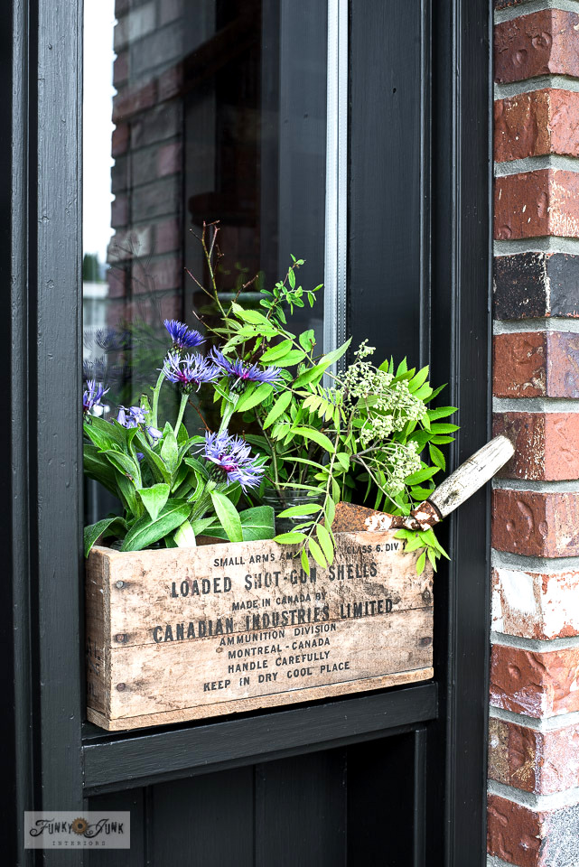 Bachelor button flowers tucked inside an antique crate for a faux window box effect by the blackish-brown front door. Visit post for painting tips and the entire tour! #flowers #frontdoor #painting
