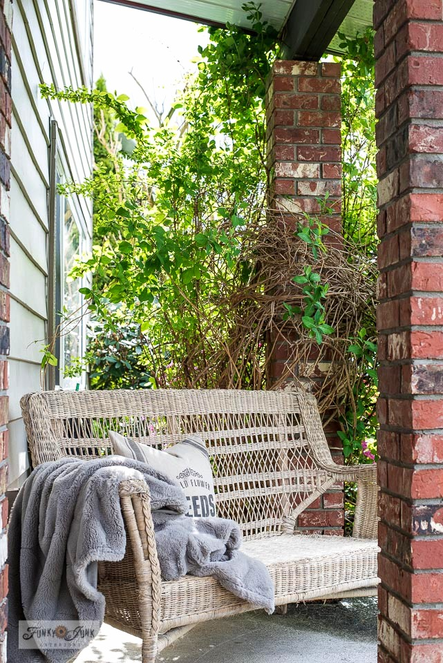 A wicker loveseat by a front door under a porch beside brick posts of wisteria. Click to take the full front porch tour!