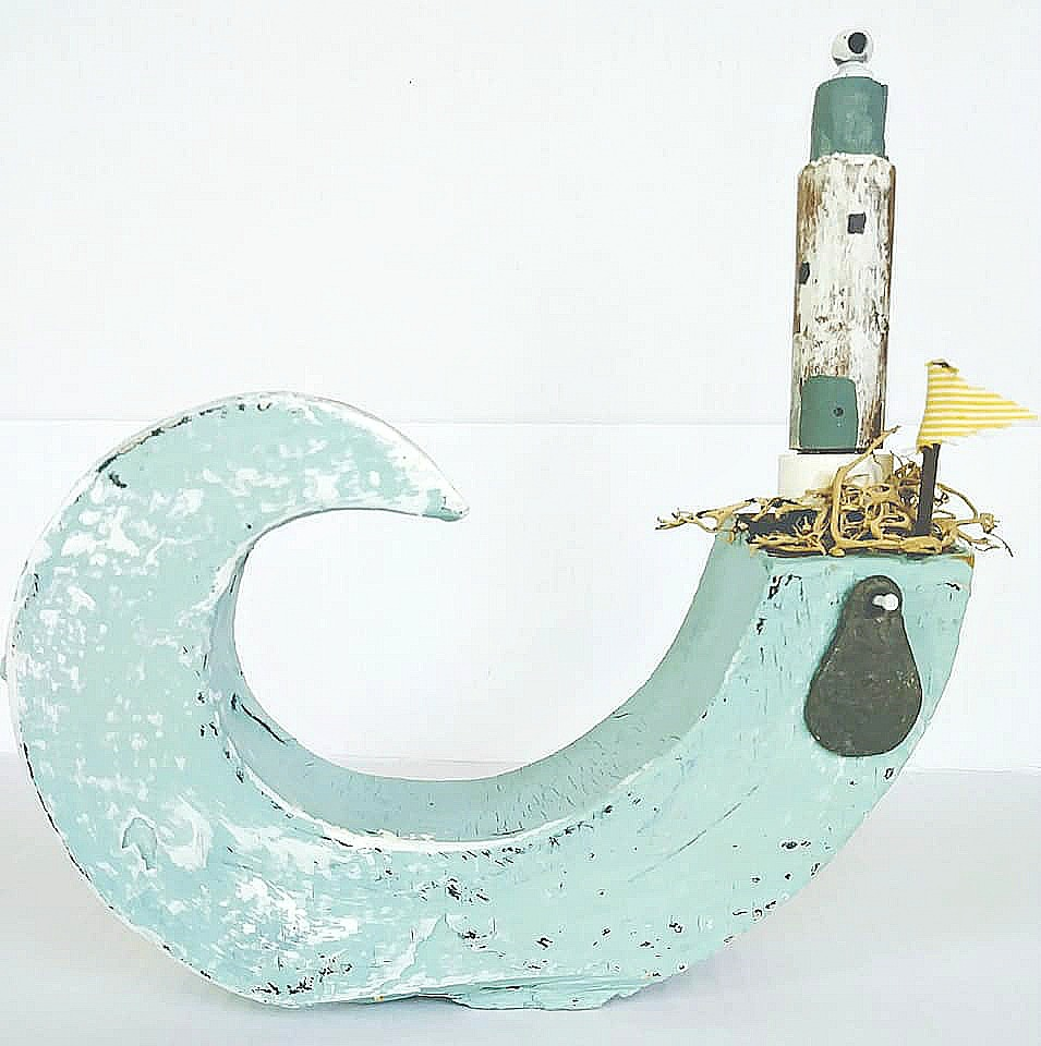 Charming scrap wood lighthouse on a wave village by Junky Encores, featured on DIY Salvaged Junk Projects 532 on Funky Junk!