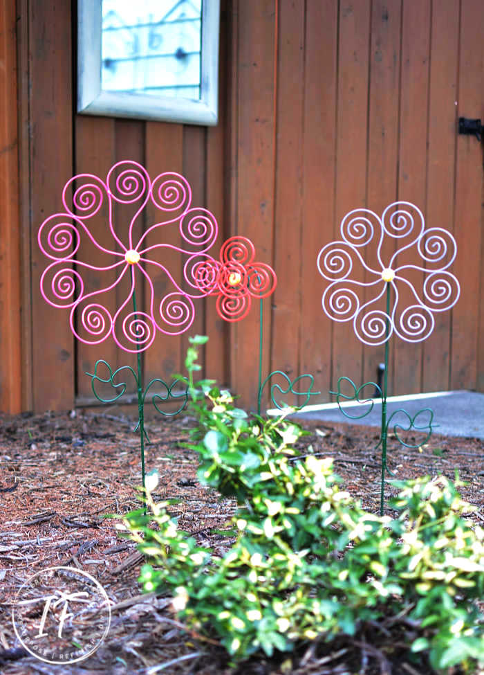 Recycled outdoor flower garden art by Interior Frugalista, featured on DIY Salvaged Junk Projects 537 on Funky Junk!