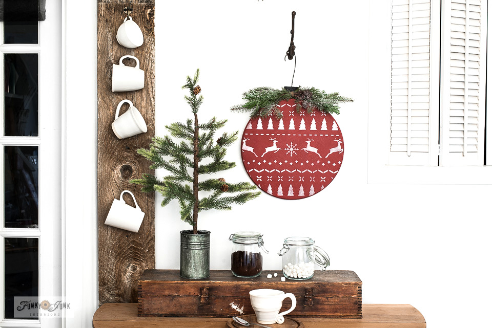 Learn how to DIY this cozy oversized wood round Christmas sweater ornament with Funky Junk's Old Sign Stencils! Perfect for Christmas decorating! Click to read full tutorial with helpful video.
