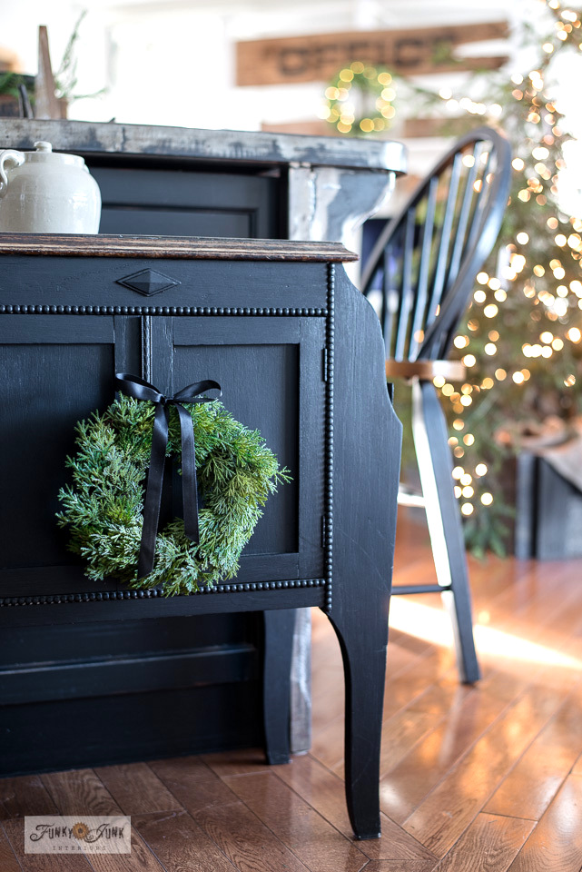A decadent side table painted in Fusion Mineral Paint's Coal Black with a pretty faux wreath with black satin ribbon, all decorated for Christmas! Click to take the full Christmas kitchen junk home tour!