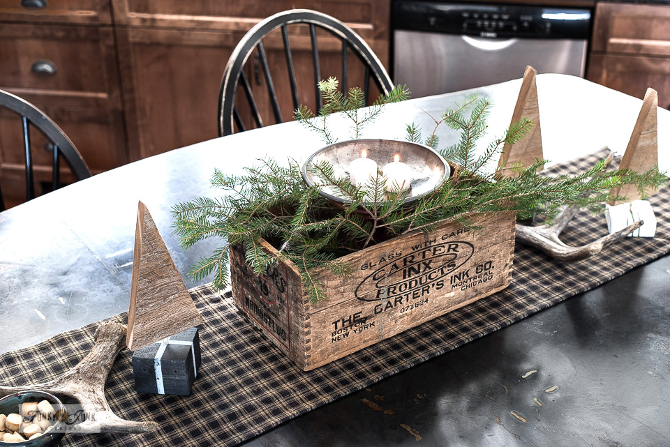 Create a charming Christmas vignette with a vintage crate, candles, scrap wood trees and antlers! Click to visit post for the full Christmas kitchen junk home tour!