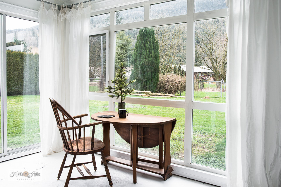 An antique wooden chair and table take in a mountain view through an all white photo studio! Take the tour and learn how to paint a concrete floor white.