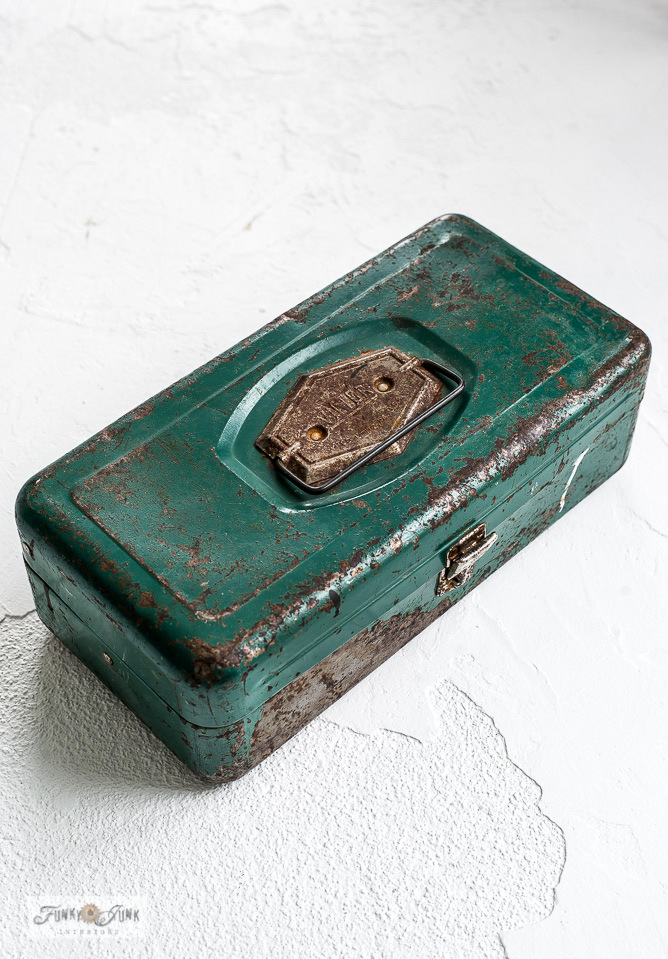 A photo shoot of a rusty green metal toolbox on a painted white concrete floor in a photo studio. Click the link to read how to paint a concrete floor white!