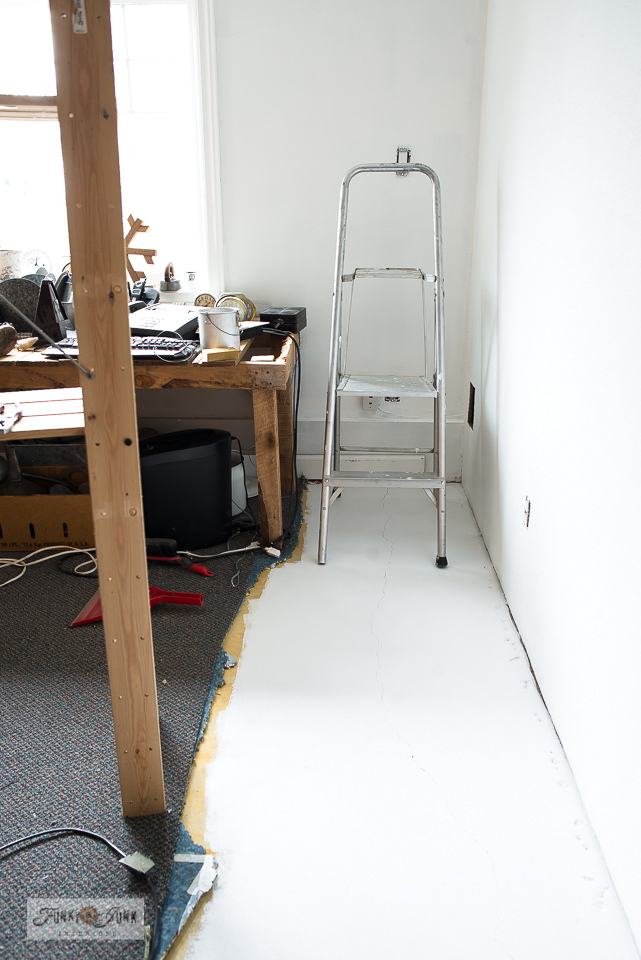 A cement floor gets painted in white to instantly brighten up this office and storage space!