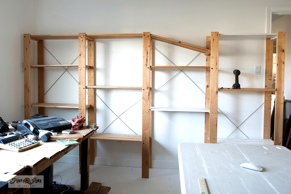 Ikea Gorm wood shelving gets put together along a full wall for lots of storage and organization.