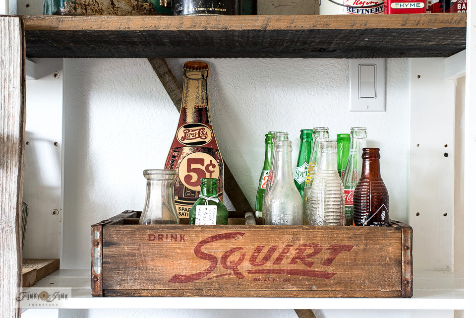 Antique Squirt crate with a collection of vintage soda pop bottles, part of a storage solution for collections.