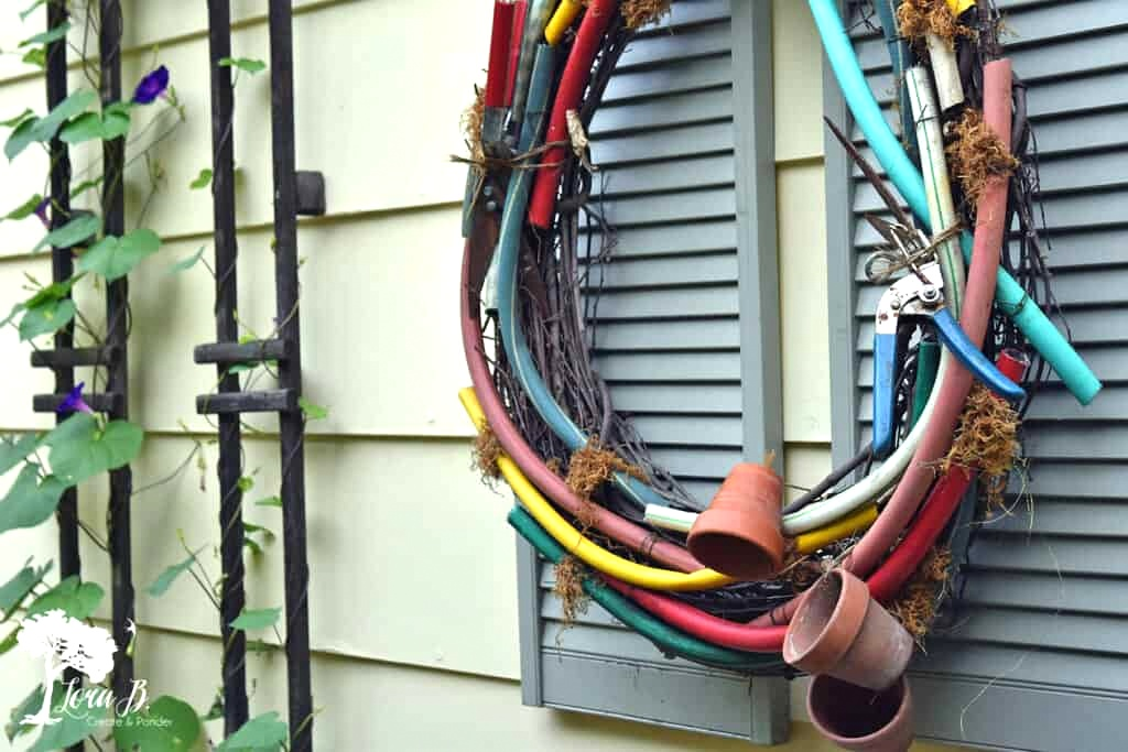Garden hose wreath by Lora B, featured on DIY Salvaged Junk Projects 573 on Funky Junk!