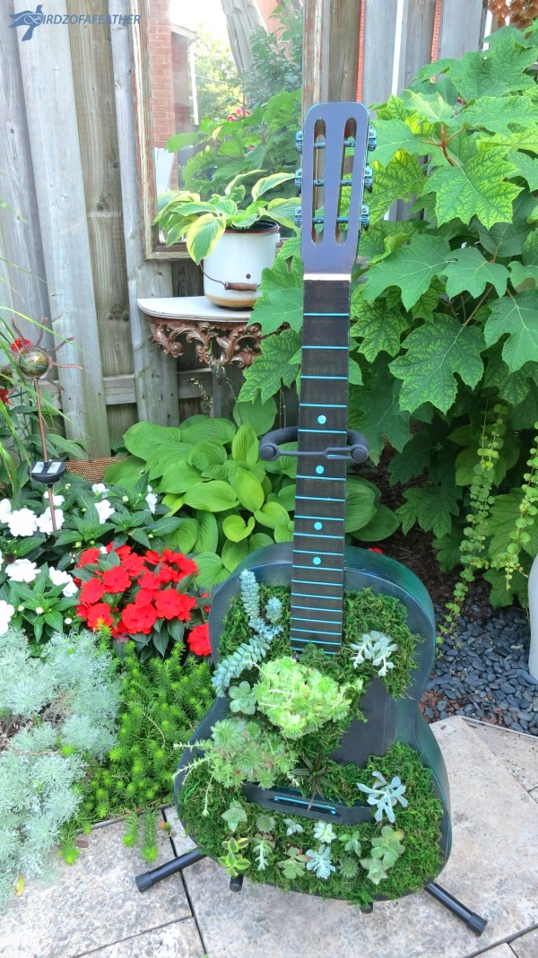 Outdoor guitar planter by Birdz of a Feather, featured on DIY Salvaged Junk Projects 573 on Funky Junk!