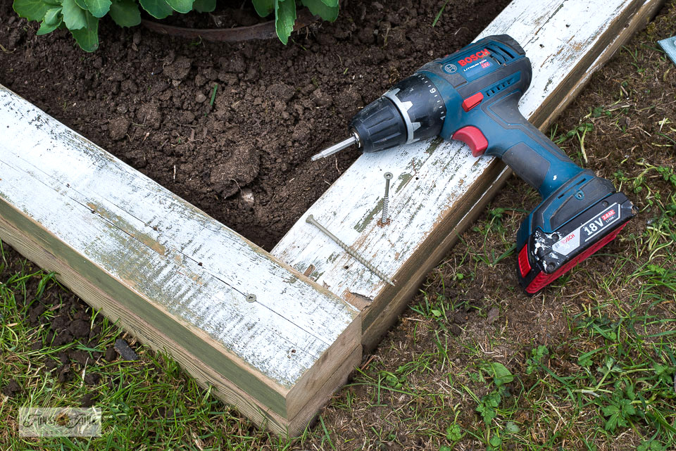 Learn how to create an easy flowerbed edge using reclaimed wood! Includes how to create a vertical Garden Shed sign too! Click for the full tutorial.