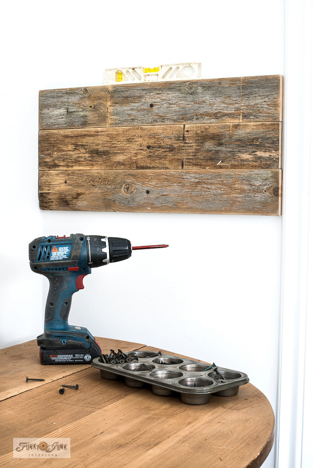 Learn how to make these industrial wood and pipe stencil storage hooks for a rustic touch! Compact and easy too! Click to read full tutorial.