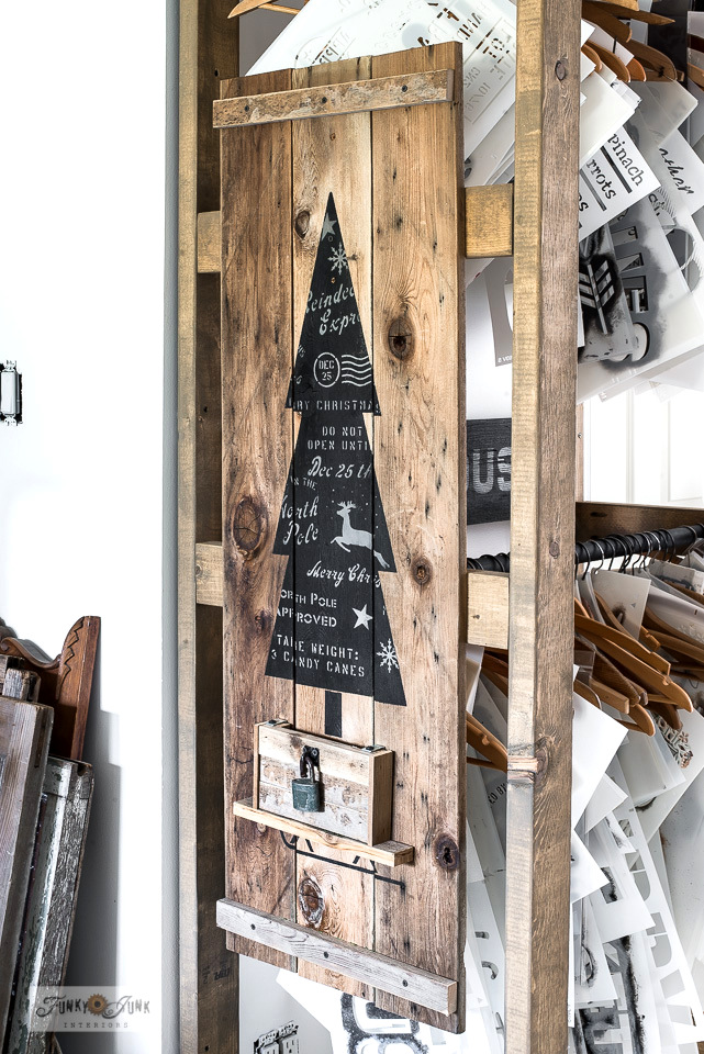 Display sample signs such as this charming vertical Christmas tree sign on reclaimed wood on a clever and easy stencil storage rack made from 2x4s!