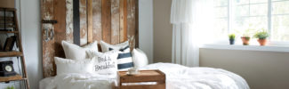 A cheater reclaimed wood barn door headboard with faux hardware